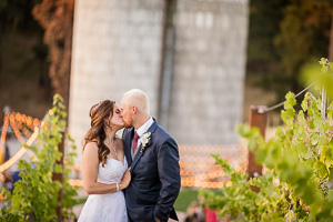 Bride and groom at Settlers Creek kissing at sunset in front of the wedding venue's silo's.