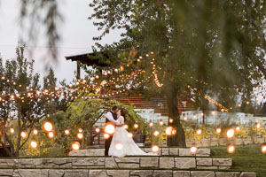The bride and groom standing on a hill under the lights kissing at dusk.