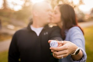 An engaged couple kissing with the sun behind them while holding a golf ball with their wedding date on it.
