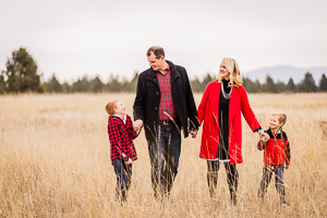 A beautiful family from Spokane Washington walking through a field and laughing just before the holidays.